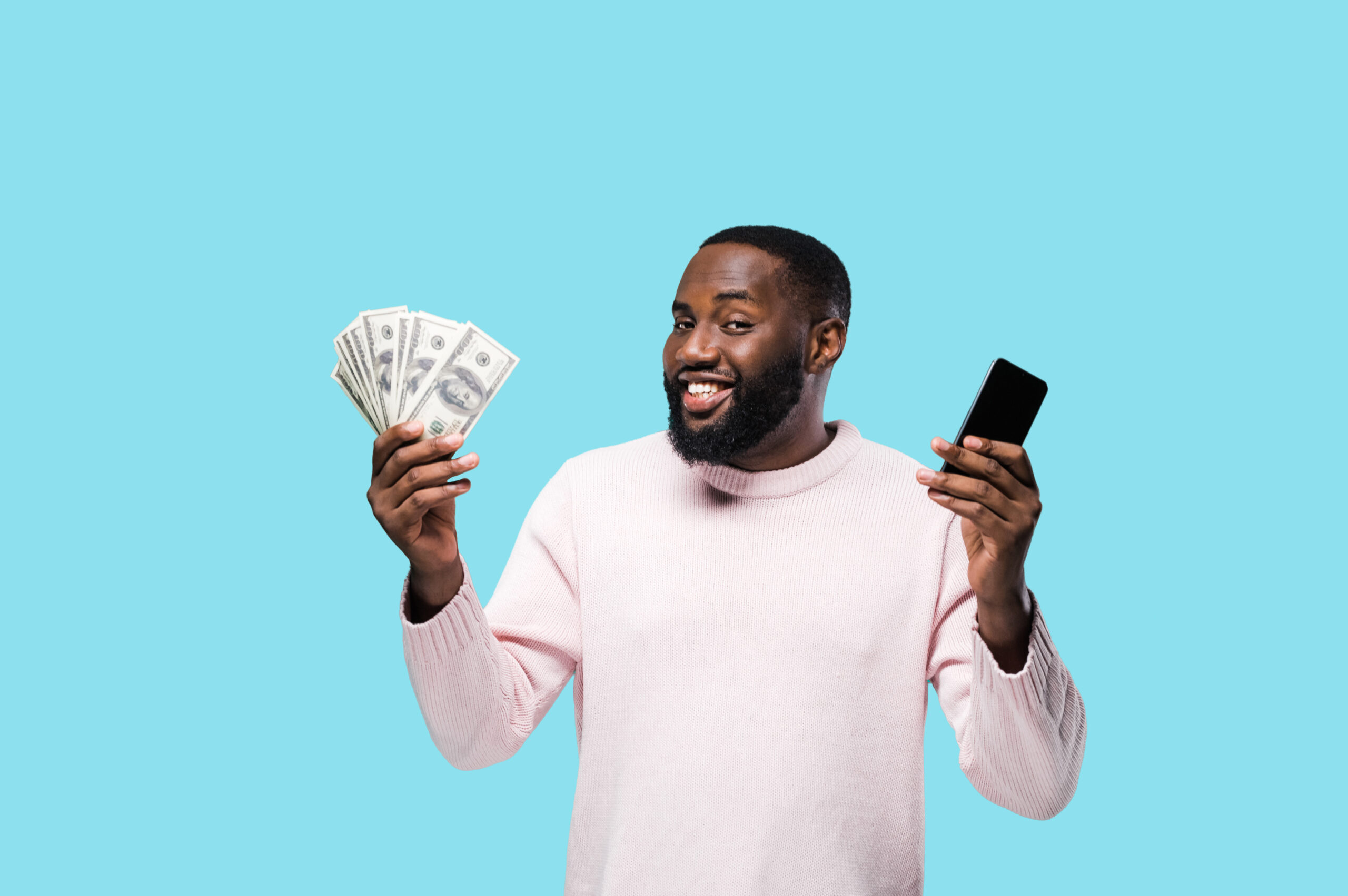 Smiling attractive african american man holds a bunch of money in his hand and mobile phone while standing on isolated blue background and looking at the camera